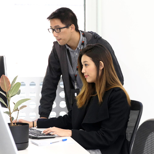 Intern working on computer with manager