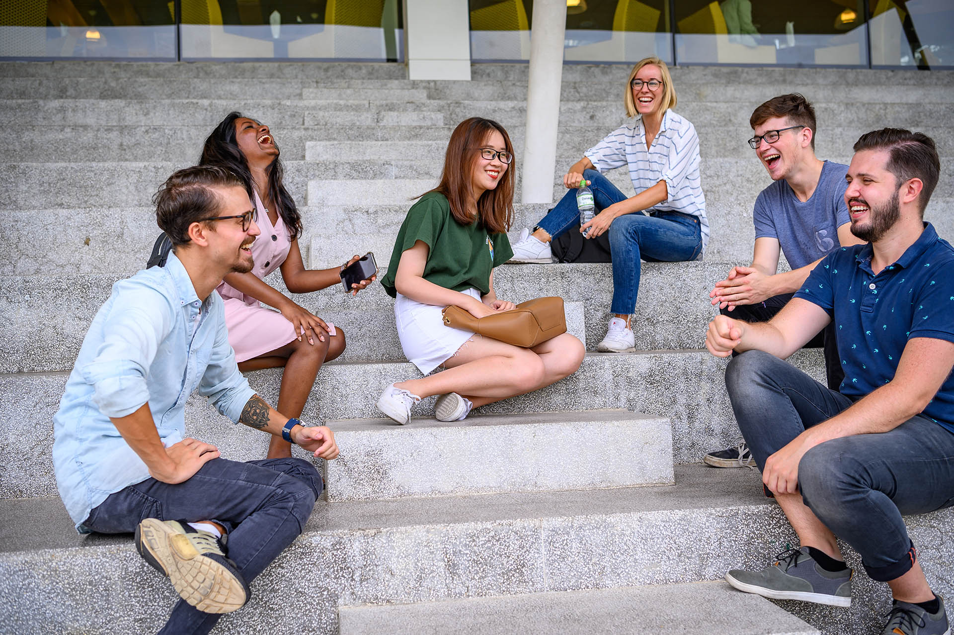 international students sitting and chatting on white stairs